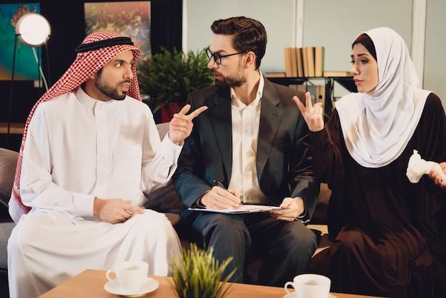 Casal árabe na recepção do terapeuta argumenta.