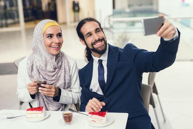 Casal árabe sentado no café e fazer selfie.