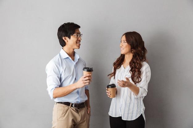 Casal asiático alegre em pé, conversando, tomando café para viagem