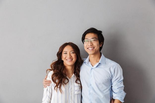 Casal asiático alegre em pé, se abraçando