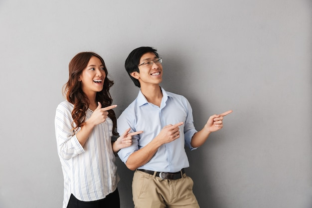 Casal asiático alegre parado isolado, apontando o dedo para a direita