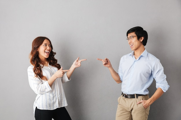 Casal asiático alegre parado isolado, apontando