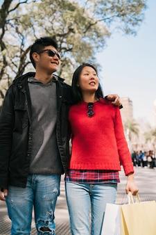 Casal asiático andando na cidade.