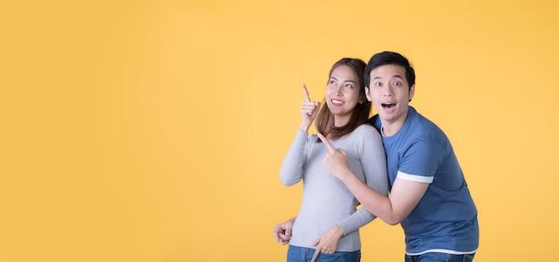 Casal asiático animado apontando o dedo para o espaço vazio da cópia do texto sobre fundo amarelo