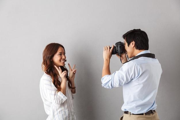 Casal asiático animado em pé isolado, tirando fotos com a câmera fotográfica