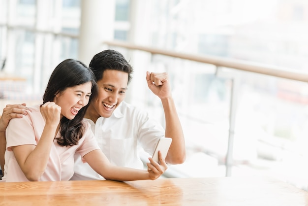 Casal asiático animado olhando para smartphone