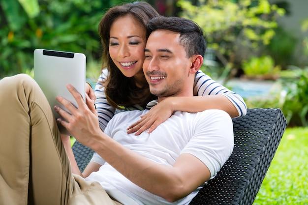 Casal asiático ao ar livre com um tablet pc