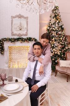Casal asiático apaixonado em roupas elegantes celebra o natal junto à lareira e à árvore em uma casa de luxo