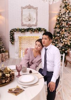 Casal asiático apaixonado, homem e mulher em trajes elegantes, abraçando-se junto à lareira e na árvore, jantar