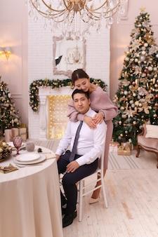 Casal asiático apaixonado, homem e mulher em trajes elegantes, se abraçando perto da lareira e da árvore