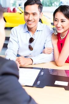 Casal asiático assinando contrato de vendas de carro na concessionária