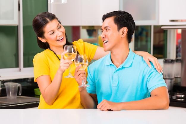 Casal asiático bebendo vinho branco em casa