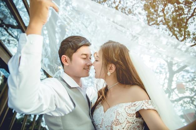 Casal asiático beijando debaixo do véu.