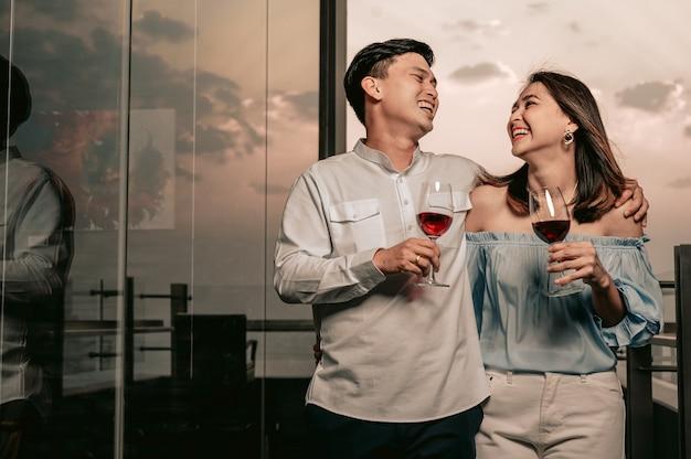Casal asiático caminhando no bate-papo e segurando taças de vinho no restaurante hotelvacationdinnerlove