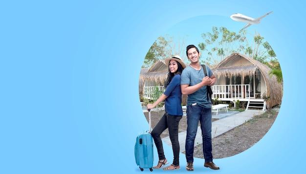 Casal asiático com mala e mochila de pé com fundo de casa de campo