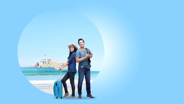 Casal asiático com mala mala e mochila de pé com fundo de areia da praia