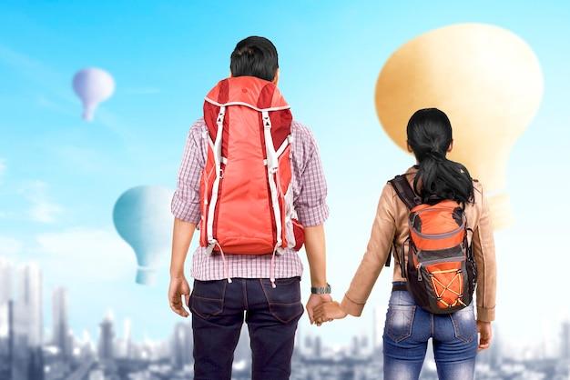 Casal asiático com mochila olhando para um balão de ar colorido voando com o fundo da cidade