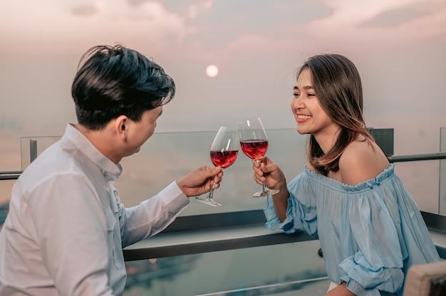 Casal asiático comemora vinho com vista romântica na mesa do restaurante hotelvacationdinner