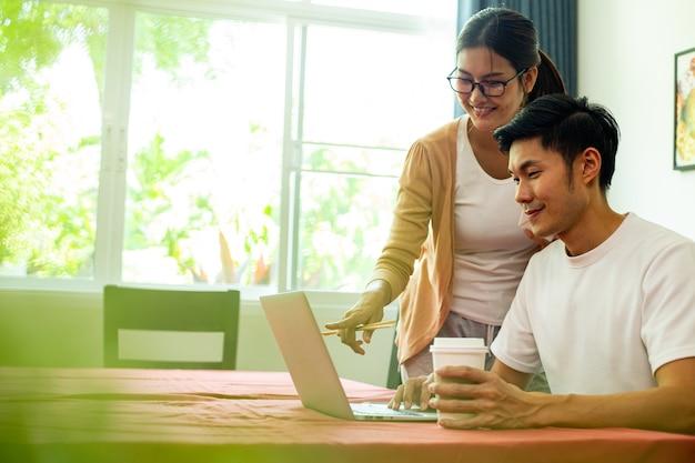 Casal asiático comendo e trabalhando juntos na cozinha. aproveite para uma refeição saudável. estilo de vida para jantar e ficar em casa. mulher comendo macarrão instantâneo.