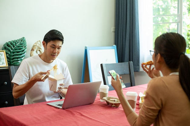Casal asiático comendo macarrão instantâneo e pizza juntos na cozinha. aproveite para uma refeição saudável. estilo de vida para jantar e ficar em casa. mulher comendo macarrão instantâneo.