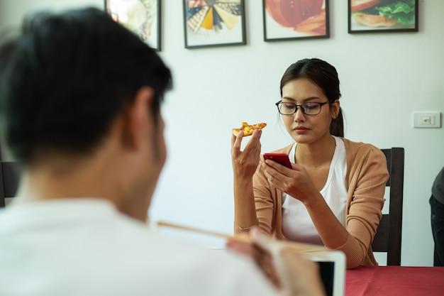 Casal asiático comendo macarrão instantâneo e pizza juntos na cozinha. aproveite para uma refeição saudável. estilo de vida para jantar e ficar em casa. mulher usando smarphone para pesquisar informações durante a alimentação.