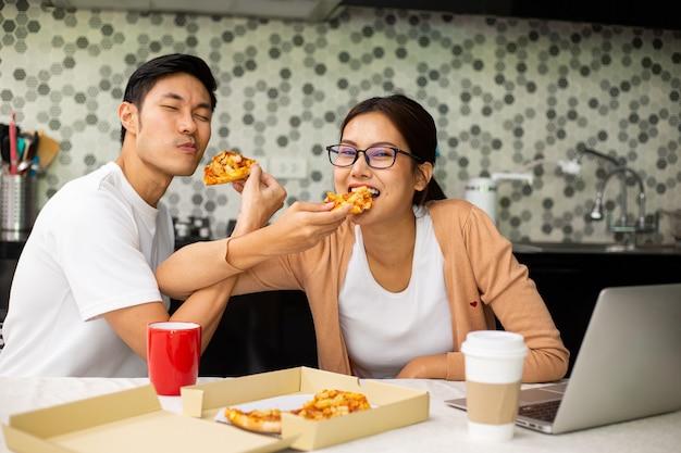 Casal asiático comendo pizza juntos na cozinha. aproveite para uma refeição saudável. estilo de vida para jantar e ficar em casa. mulher comendo macarrão instantâneo.