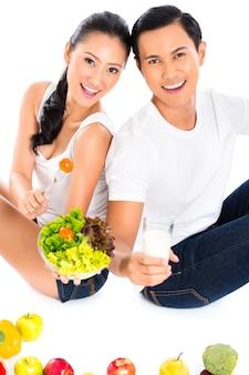 Casal asiático comendo salada de frutas e vegetais