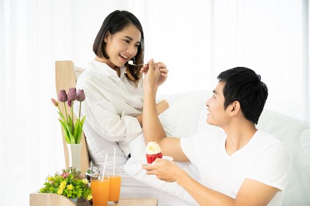 Casal asiático comendo um bolo e suco de laranja no quarto, casal fofo.