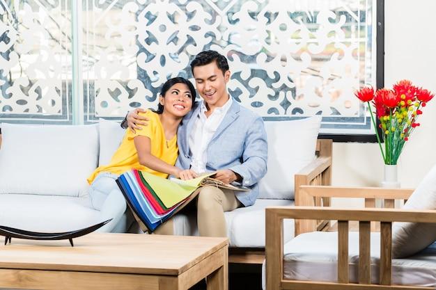 Casal asiático comprando sofá na loja de móveis