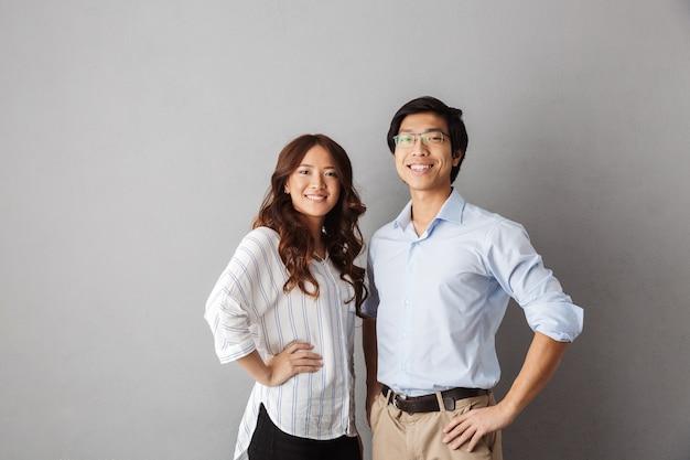 Casal asiático confiante posando sorrindo