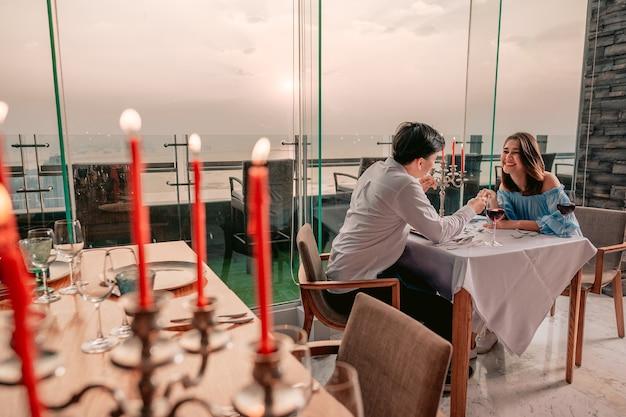 Casal asiático conversa alegremente com vista romântica na mesa do restaurante hotelvacationdinner
