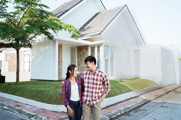 Casal asiático dançando na frente de sua casa nova