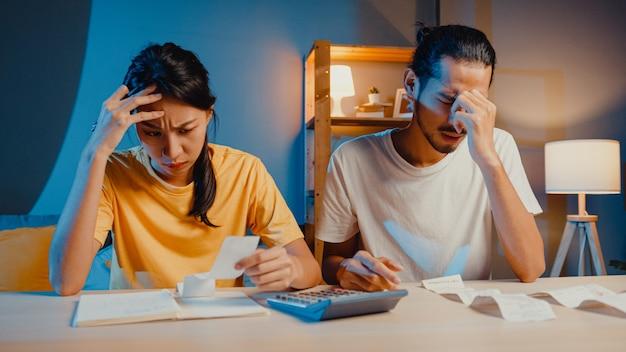 Casal asiático de estresse, homem e mulher, usam calculadora para calcular o orçamento familiar
