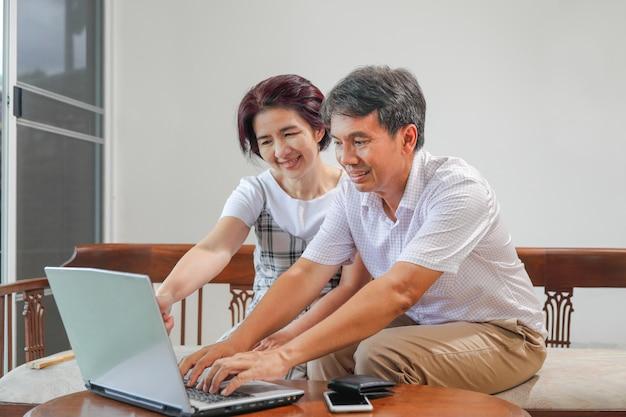 Casal asiático de meia idade trabalha em casa