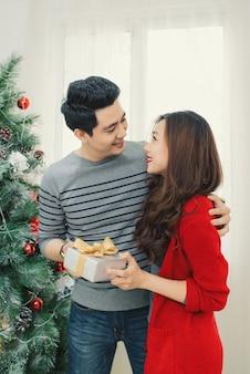 Casal asiático de natal. um homem bonito dando um presente em casa para sua namorada / esposa comemorando o ano novo.