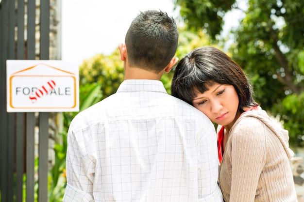 Casal asiático decepcionado na frente de uma casa