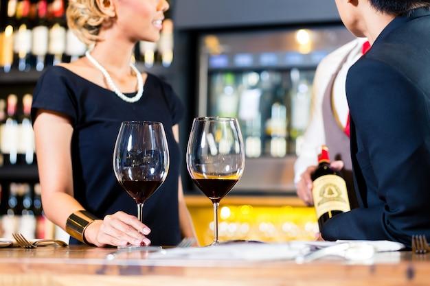 Casal asiático degustando vinho tinto em um barril de vinho