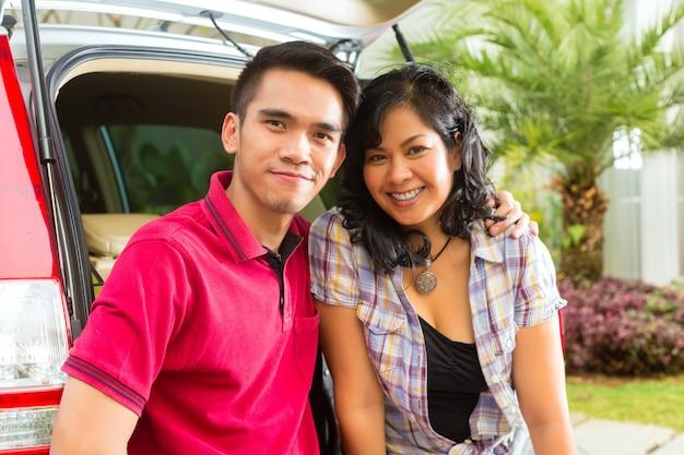 Casal asiático é feliz na frente do carro