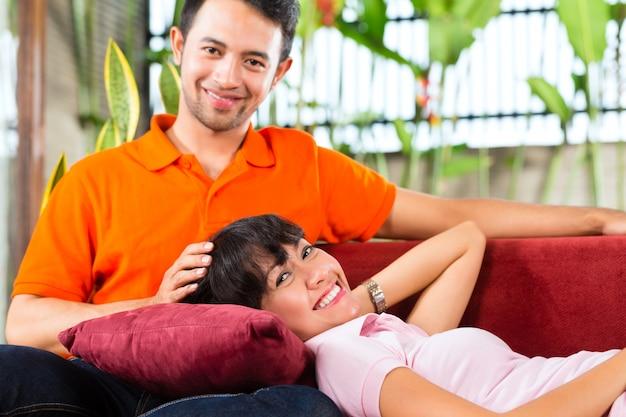 Casal asiático em casa espaçosa no sofá