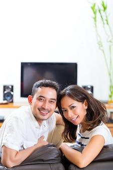 Casal asiático em casa na sua sala de estar