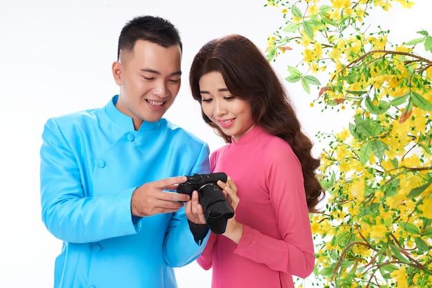 Casal asiático em traje tradicional brilhante, verificando fotos na câmera ao lado de mimosa florescendo