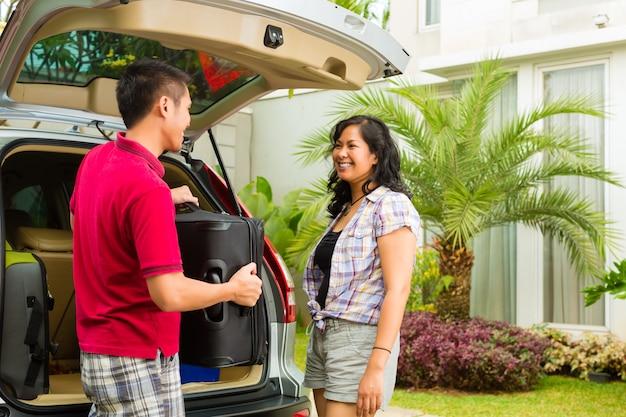 Casal asiático, embalagem de carro com malas para férias