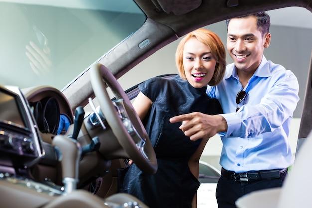 Casal asiático escolhendo carro de luxo em concessionária, olhando para o interior