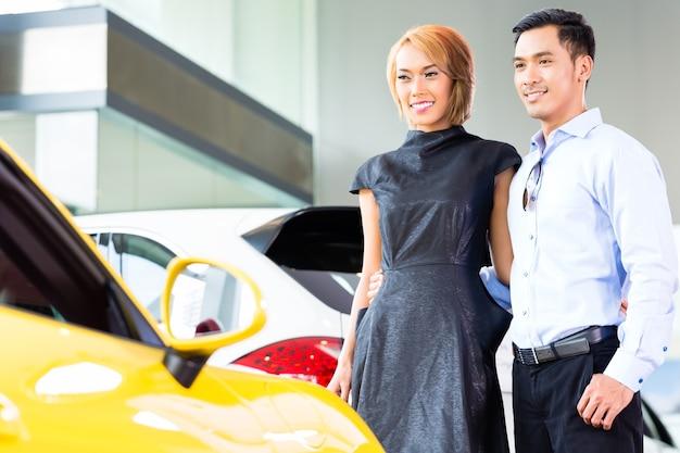 Casal asiático escolhendo carro esporte de luxo em concessionária olhando para um roadster