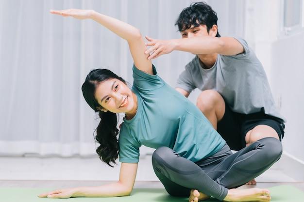 Casal asiático fazendo ioga juntos em casa