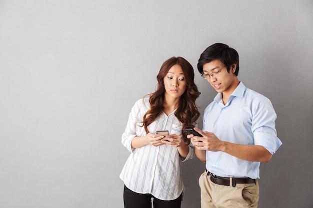 Casal asiático feliz isolado, usando telefones celulares
