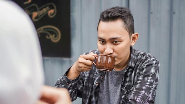 Casal asiático feliz namoro se encontra em um café e bebe café
