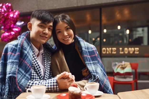 Casal asiático feliz no amor celebração no café.