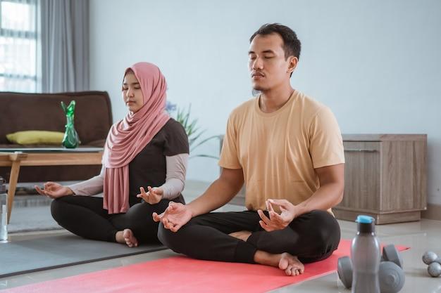 Casal asiático fitness, homem e mulher se exercitando juntos fazendo ioga