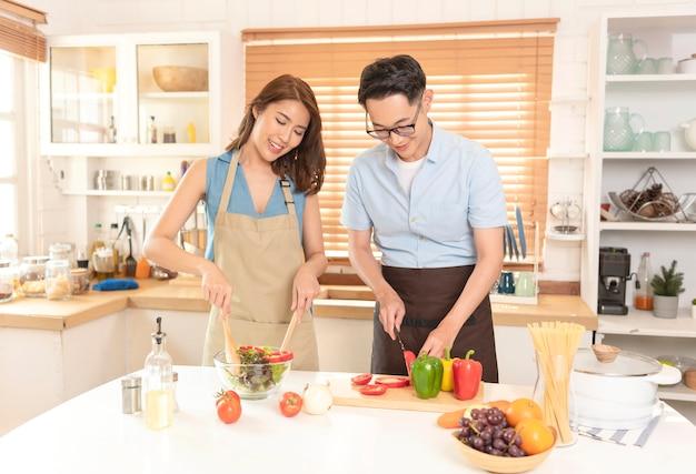 Casal asiático gosta de cozinhar salada juntos na sala da cozinha em casa.